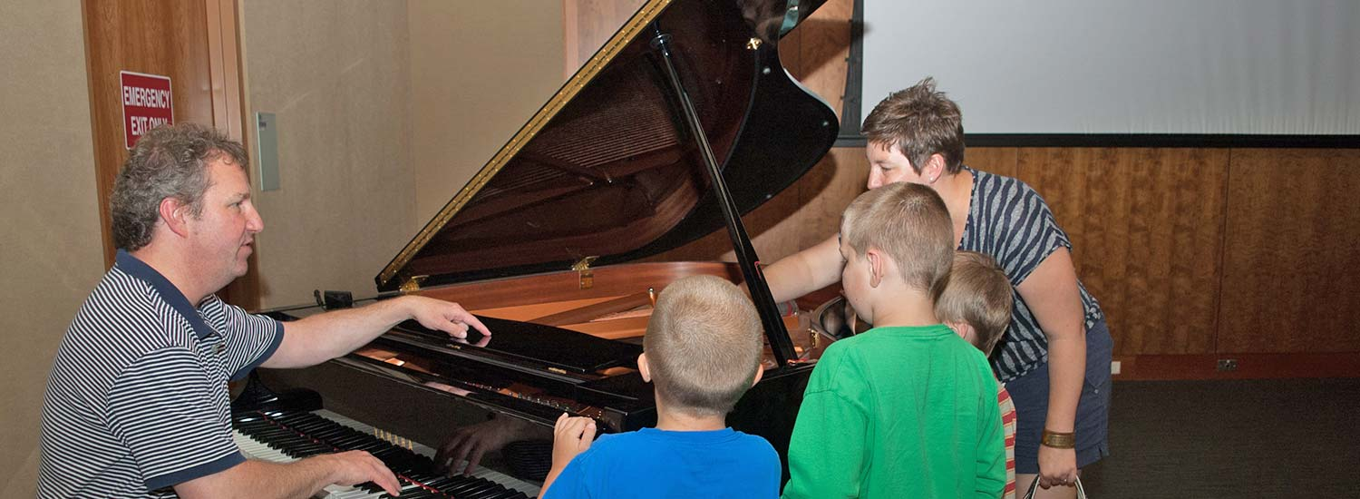 Father and kids gathered around Piano
